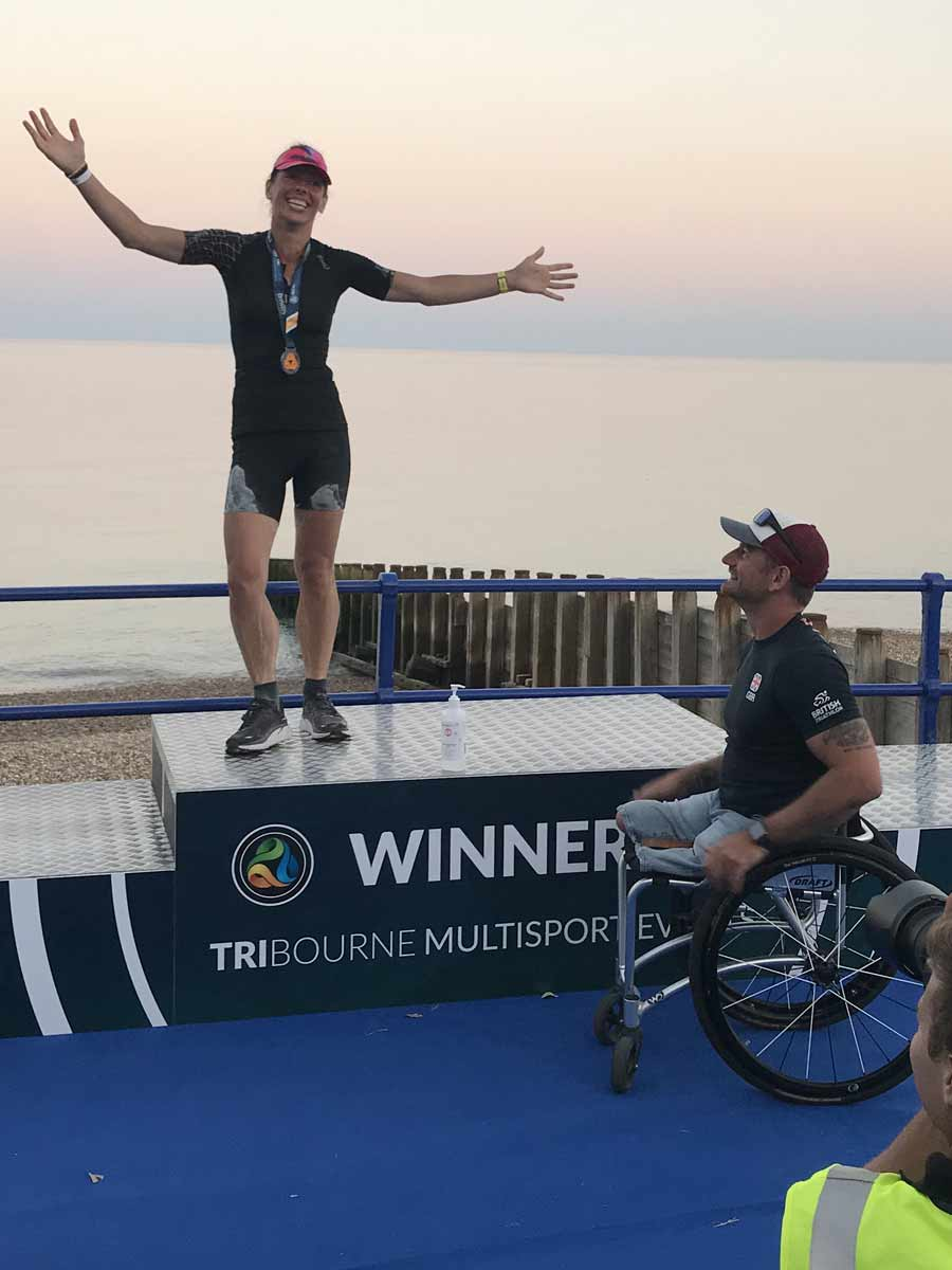 Joe Townsend, former commonwealth para triathlon champion presenting her with the award for winner of female 45-49 years category for the full distance event.
